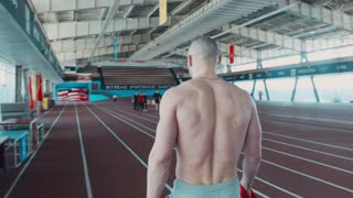 The tired sprinter topless, the athlete goes on a running track, prepares for start. Part of muscular body. Wide movement shot.