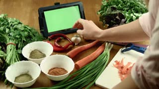 The woman cooks food and watches the recipe in the tablet with greenscreen