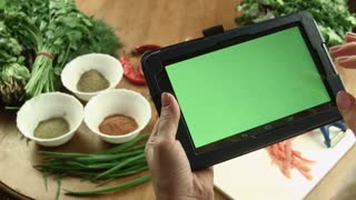 The woman cooks food and watches the recipe in the tablet