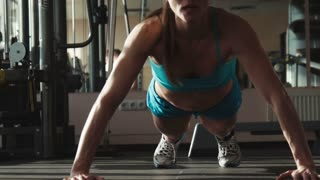 The woman in sportswear does push-ups in a gym