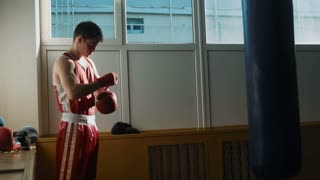 The young boxer puts on gloves and starts boxing a punching bag