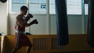 The young boxer training in gym with punching bag
