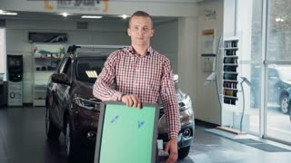 Three Quarter Length Portrait of Smiling Man Wearing Checkered Shirt Standing inside Car Dealership in front of Shiny New Vehicle and Holding Blank Green Sign with Copy Space. 4K