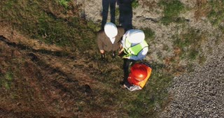 Three technicians, builders, workmen or architects wearing hardhats having a meeting outdoors, on site in a field, overhead view