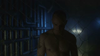 Topless sexy prisoner with metal chain in hands holding fence while looking agressively at camera