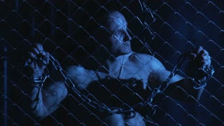 Topless sexy prisoner with metal chain in hands in moonlight holding fence while looking agressively at camera