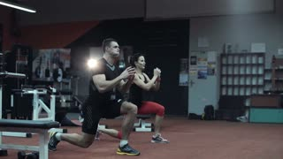 Two fit young athletes doing cardiovascular exercises in a darkened gym in a running motion with raised hands as they work out together in a healthy active lifestyle concept