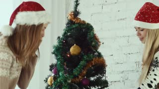 Two girlfriends decorate the Christmas tree