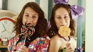 Two girls lick candies and show them in the camera