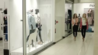 Two girls look at a show-window on dummy of shop