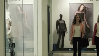 Two girls look at a show-window of shop