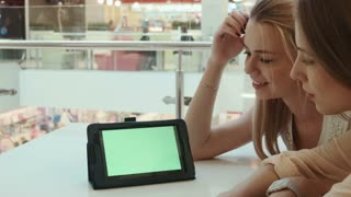 Two girls look at the tablet with the green screen