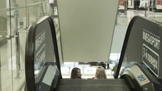 Two girls rise on the escalator