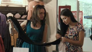 Two girls try on shirts in clothes shop