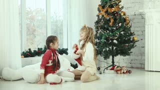 Two girls wear Santa hats to one another