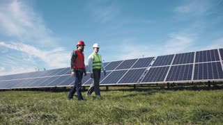 Two male electrician workers in reflective vests and hard hats walking in between long rows of photovoltaic solar panels and talking about installation of new solar panels