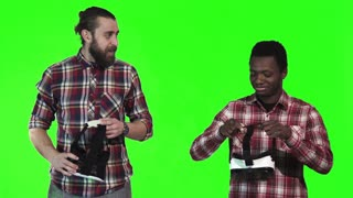 Two man caucasian bearded and farican, wearing VR googles on green screen and start to fight