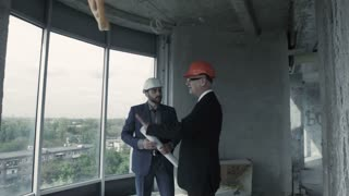 Two men in suit and helmet discuss blueprint, calculate and communicate with colleague. American man, designer, show plan to chief engineer builder indoor unfinished building, present project of smart