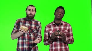 Two multiracial men eating black and white hamburgers, one a bearded Caucasian and the other a young black guy, upper body isolated on green screen. The looking at camera