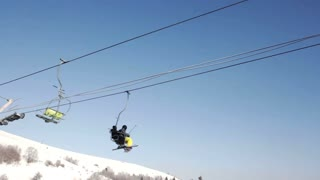 Two skiers riding up ski lift