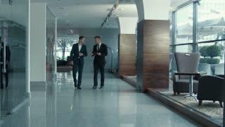 Two walking indoor businessman