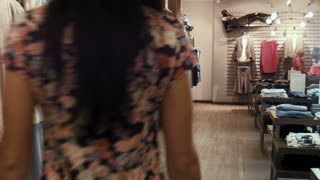 Two young girls choose clothes in shop