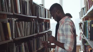 Two young men standing in library and choosing the books. Then African student weared eyeglasses turn to camera and smile