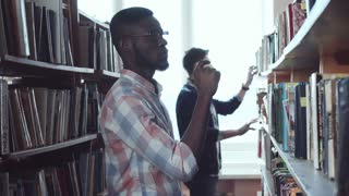 Two young men standing in library and choosing the books