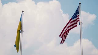 Ukraine and United States flags fluttering in wind with bright sky in background