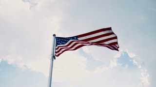 United States American flag flying from a flagpole in a wind showing the stars and stripes against a cloudy blue sky in a patriotic image