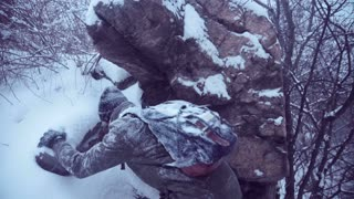 Unrecognizable man in snowy clothes with backpack trying to climb rock in winter woods then he holding portable radio set and trying to catch a signal in blizzard
