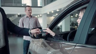 Unrecognizable Sales Manager Gives the Client the Keys from the Car. Then smiling woman customer look straight at the camera, while her husband standing in the background