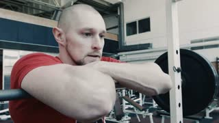 Very tired athlete after workout near barbell bar breathing and looking at camera.
