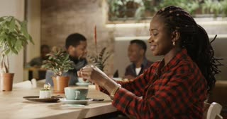 A beautiful casual black girl pours sugar into coffee and stirs it sitting in a cozy cafeteria