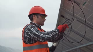 A builder looking at camera and working with the solar energy panels