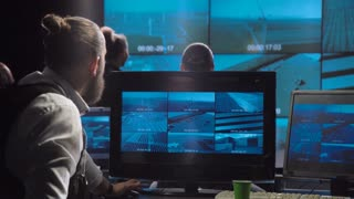 A special forces surveillance team in a futuristic office with large live screens
