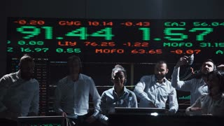 A stock broker team celebrating beside a live global market feed