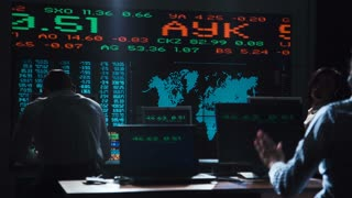 A woman stock broker working in futuristic office with live global market feed displays