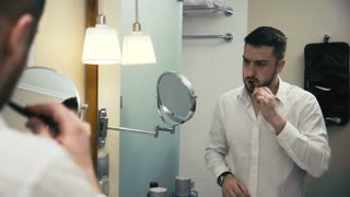 Adult bearded man being in business trip standing in front of mirror in hotel bathroom and brushing teeth.