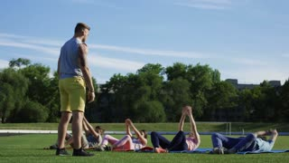Adult man and woman with children lying on mats on green grass of stadium and doing abdomen exercise all together with personal trainer
