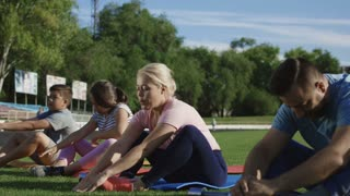 Adult man and woman with children lying on mats on green grass of stadium and doing abdomen exercise all together