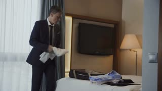 Adult man in suit having phone call meanwhile packing suitcase leaving hotel room at end of business trip.
