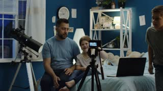 Adult man with girl and boy recording live stream for vlog while sitting on bed and reading comments from laptop giving answers