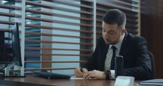 Adult manager in suit writing on paper and looking at camera in office