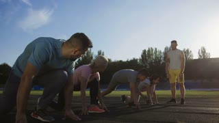 Adult parents and kids starting sprint and challenging in time score on racetrack of stadium with personal trainer standing