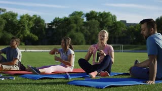 Adult parents and teen kids refreshing with water while sitting on mats on green athletic field and having break in workout