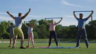Adult parents with teen children doing exercise with sticks on green field under control of personal trainer