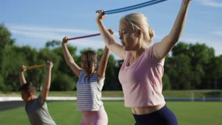 Adult serious woman and children doing exercise with fitness stick on field in summer sunlight