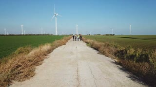 Aerial shot of four engineers wearing hardhat walking against turbines at wind farm on sunny day