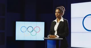 African American anchor reading Olympic news in front of the Olympic symbol panning to the left to one of the production team